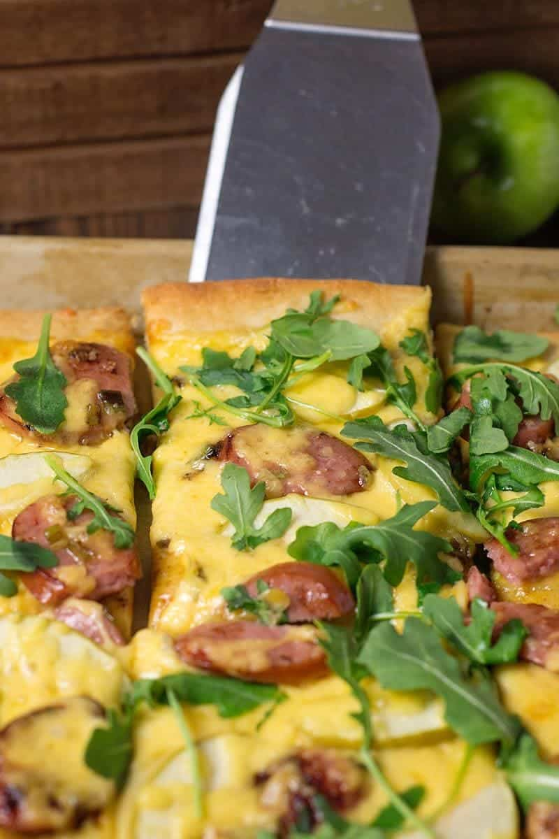 pizza with sausage, gouda and arugula