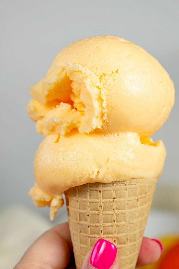homemade orange sherbet in a sugar cone