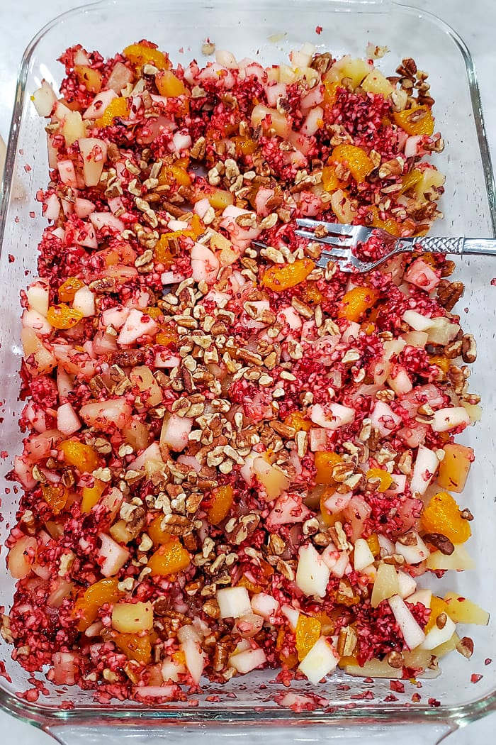 the fruit and nut mixture in a cranberry jello salad